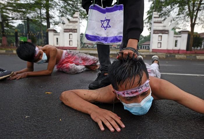 Sejumlah aktivis HMI (Himpunan Mahasiswa Islam) Banten berunjuk rasa dengan menggelar aksi teatrikal memprotes kekejaman Israel terhadap warga Palestina di Alun-alun Serang, Banten, Senin (17/5/2021). Mereka menyerukan warga Dunia untuk bersatu melawan kesewenang-wenangan Israel dan menolong warga Palestina agar terbebas dari penindasan. ANTARA FOTO/Asep Fathulrahman/wsj.