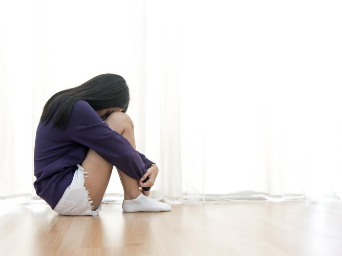 Sad young woman sit in her room and covering her face