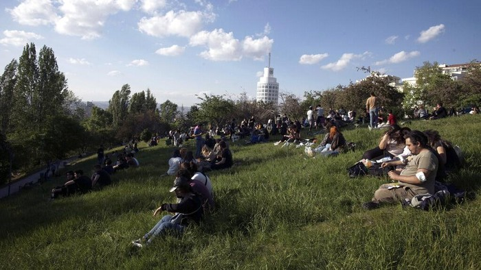 People enjoy the good weather at a park, hours after a 17-day full lockdown ended, in Ankara, Turkey, Monday, May 17, 2021. Turkey's daily COVID-19 infections have dropped to levels last seen in mid-March as the country ended its strictest restrictions.(AP Photo/Burhan Ozbilici)