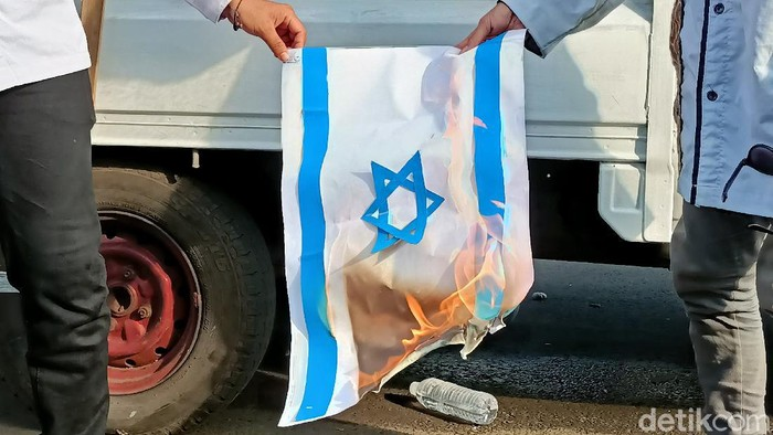 Massa aksi bela Palestina bakar replika Bendera Palestina di depan Kedubes AS