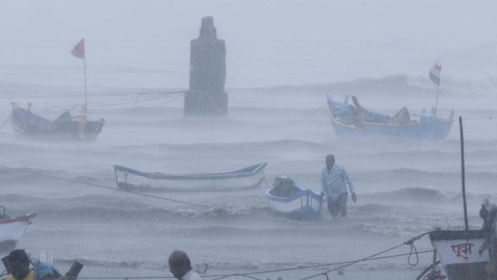 A fisherman waits for help as he tries to move a fishing boat to a safer ground on the Arabian Sea coast in Mumbai, India, Monday, May 17, 2021. Cyclone Tauktae, roaring in the Arabian Sea was moving toward Indias western coast on Monday as authorities tried to evacuate hundreds of thousands of people and suspended COVID-19 vaccinations in one state. (AP Photo/Rafiq Maqbool)