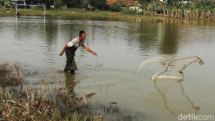Lapangan sepak bola, di Rawa Tengah, Cikiwul, Kota Bekasi, yang terendam banjir dimanfaatkan sejumlah warga untuk memancing ikan.