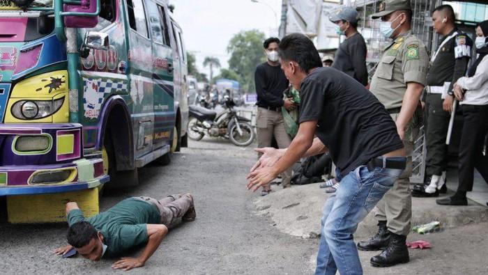 Sopir membawa penumpang di atap angkutan dihukum push up di posko penyekatan larangan mudik Lebaran, Jalan Jamin Ginting, Medan, Senin (17/5) (ANTARA/HO)