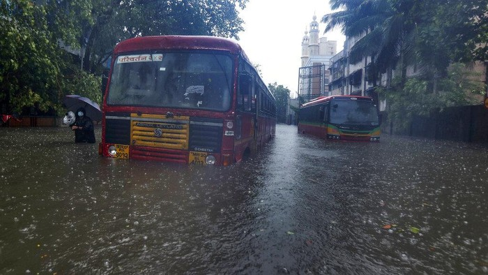 Buses are stranded on a waterlogged road during heavy rain in Mumbai, India, Monday, May 17, 2021. Cyclone Tauktae, roaring in the Arabian Sea was moving toward India's western coast on Monday as authorities tried to evacuate hundreds of thousands of people and suspended COVID-19 vaccinations in one state. (AP Photo/Rafiq Maqbool)