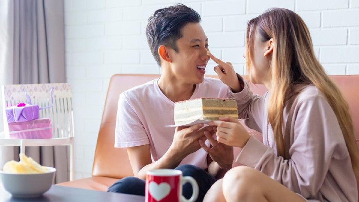 playful young asian couple celebrating Anniversary together at home, playing with the cake