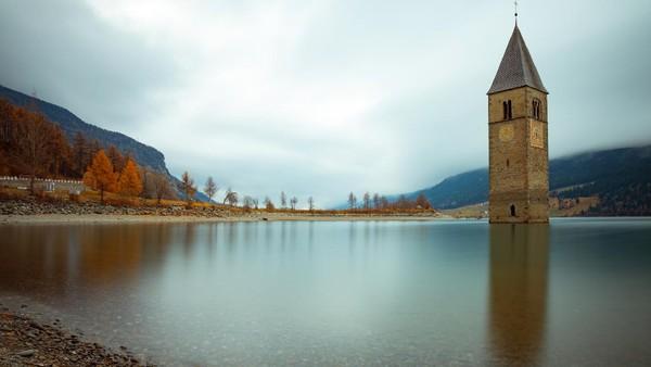 Seperti ini penampakan danau Resia saat terendam air, hanya menyisakan menara gereja dari abad ke-14. Pemandangan yang cukup mengerikan ini jadi inspirasi serial Netflix dan jadi destinasi yang cukup populer di kalangan traveler. (Getty Images/iStockphoto/Marco_Piunti)