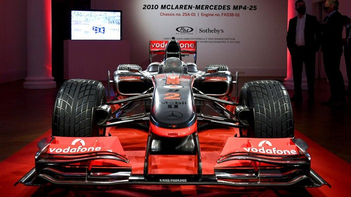 A member of staff stands by Lewis Hamilton's 2010 Turkish GP McLaren Mercedes MP4-25A, at Sotheby's, in London, Tuesday, May 18, 2021. It is the first Grand Prix winning car driven by Lewis Hamilton to come to market and will be auctioned for an estimated of 5,000,000 - 7,000,000 US dollars on July 17.  (AP Photo/Alberto Pezzali)
