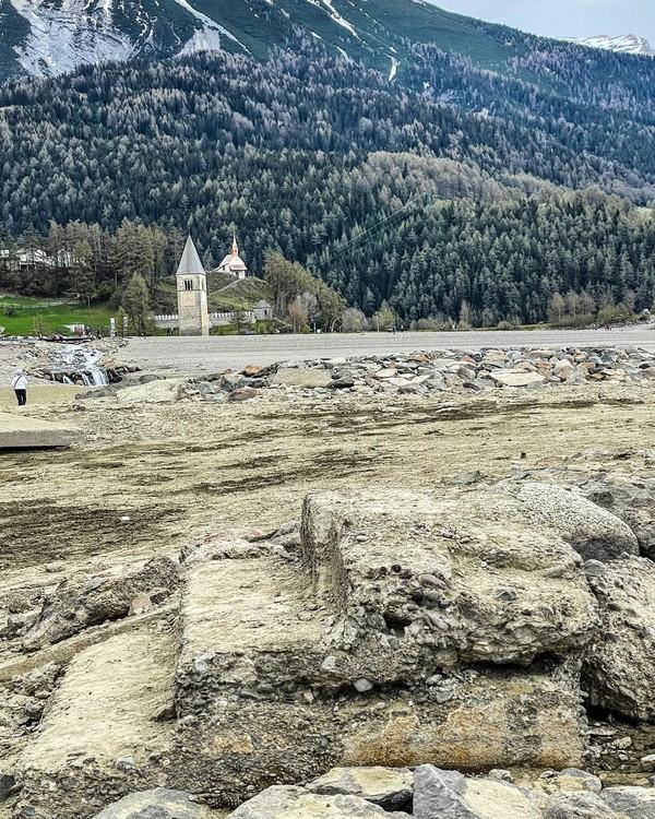 Reruntuhan desa Curon yang kembali muncul ke permukaan akibat mengeringnya Danau Resia ini bisa dinikmati warga setempat dan wisatawan. Mereka bisa melihat sisa-sisa reruntuhan desa tersebut dengan lebih dekat. Louisa Azzolini/Twitter)