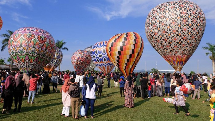 Sejumlah warga menyaksikan penerbangan balon udara di lapangan desa Kembaran, Kalikajar, Wonosobo, Jateng, Rabu (19/5/2021). Tradisi penerbangan balon udara tradisional rutin dilaksanakan masyarakat setempat pada hari ke tujuh Lebaran, agar tidak mengganggu lalu lintas udara balon udara ditambatkan menggunakan tali dengan ketinggian tertentu. ANTARA FOTO/Anis Efizudin/hp.