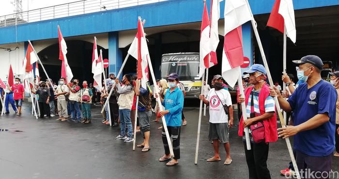Karyawan, anggota komunitas serta pedagang di Terminal Tirtonadi, Solo, Jawa Tengah (Jateng) memperingati Hari Kebangkitan Nasional (Harkitnas), Kamis (20/5/2021). Peringatan diadakan tepak pukul 10.00 WIB ini dengan mengibarkan bendera merah putih dan menyanyikan lagu Indonesia Raya.