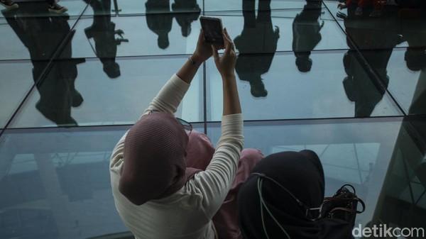 Sejumlah warga berfoto di area lantai kaca Pondok Indah Mall 3, Jakarta, Kamis (20/5/2021).