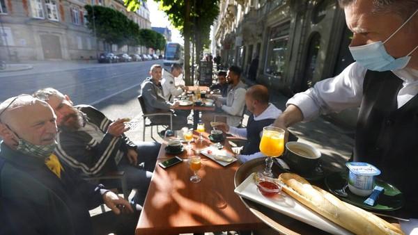 Warga Paris menikmati minuman di teras kafe di Paris, Rabu (19/5/2021) waktu setempat. Prancis telah melonggarkan lockdown karena COVID-19 mulai Rabu (19/5/2021). Restoran, museum, dan bioskop dibuka lagi. AP Photo/Jean-Francois Badias