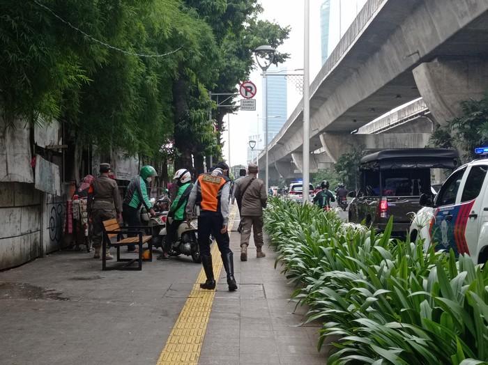 Petugas berjaga di Jl Prof Dr Satrio, Kuningan, Jakarta Selatan.