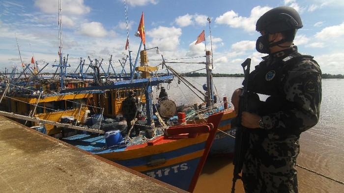 Sejumlah petugas berdiri di atas kapal ikan ilegal berbendera Vietnam di Dermaga Stasiun Pengawasan Sumber Daya Kelautan dan Perikanan (PSDKP) Pontianak di Kabupaten Kubu Raya, Kalimantan Barat, Kamis (20/5/2021). Dalam Operasi Lebaran yang dilaksanakan pada liburan Idul Fitri 2021, Kapal Pengawas Hiu Macan 01 Kementerian Kelautan dan Perikanan (KKP) yang dinahkodai Kapten Samson menangkap enam kapal ikan asing berbendera Vietnam beserta 36 Anak Buah Kapal (ABK) saat sedang menjaring cumi-cumi secara ilegal di Laut Natuna Utara pada Minggu (16/5/2021). ANTARA FOTO/Jessica Helena Wuysang/foc.
