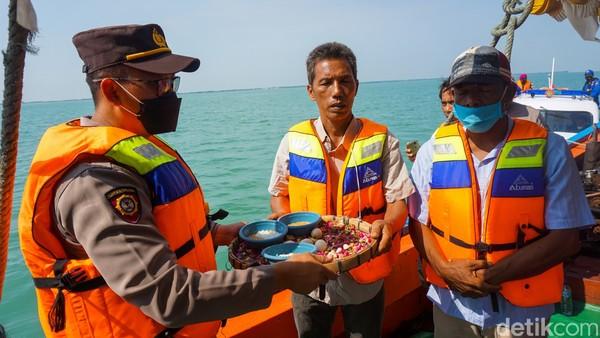 Larungan atau berdoa bersama di laut tersebut terlaksana dengan hanya doa dan makan bersama.(Mochamad Saifudin/detikcom)
