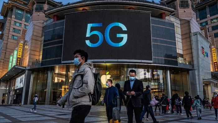 BEIJING, CHINA - April 16: Orang-orang berdiri di depan toko Apple yang mengiklankan ponsel berkemampuan 5G pada 16 April 2021 di sebuah distrik perbelanjaan di Beijing, Cina. China mengumumkan pertumbuhan ekonomi yang kuat sebesar 18,3 persen pada kuartal pertama 2021, dibandingkan dengan periode yang sama tahun lalu ketika ekonomi terbesar kedua di dunia itu terhenti karena pandemi COVID-19. (Photo by Kevin Frayer/Getty Images)