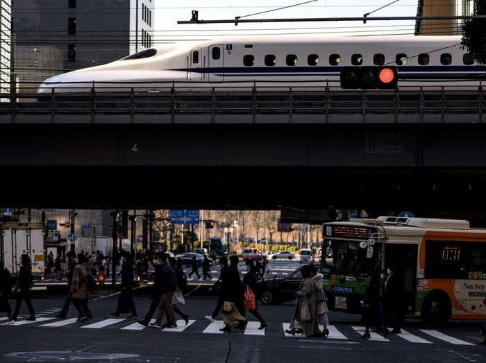 People cross a street while a shinkansen, or high speed bullet train, arrives in Tokyo on February 6, 2021. (Photo by Charly TRIBALLEAU / AFP)