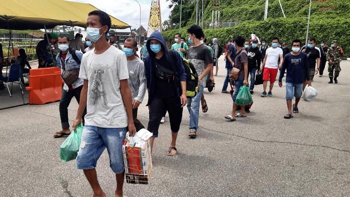 Sejumlah Pekerja Migran Indonesia (PMI) dari Malaysia memasuki perbatasan Indonesia di Pos Lintas Batas Negara (PLBN) Entikong, Kabupaten Sanggau, Kalimantan Barat, Kamis (20/05/2021). Malaysia mendeportasi 59 PMI bermasalah karena melanggar undang-undang keimigrasian setempat usai pemberlakuan larangan mudik lebaran. Selanjutnya puluhan PMI itu harus menjalani pemeriksaan kesehatan serta karantina di Terminal Barang Internasional Entikong sebelum dipulangkan ke daerah masing-masing. ANTARA FOTO/Agus Alfian/jhw/foc.