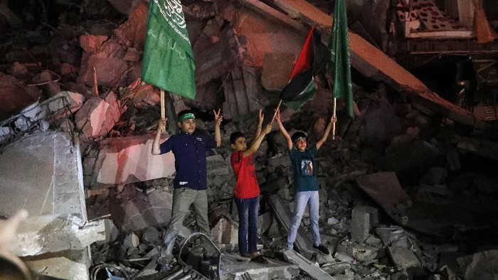Palestinians wave green Hamas flags while celebrating the cease-fire agreement between Israel and Hamas in Gaza City, early Friday, May 21, 2021. (AP Photo/Adel Hana)
