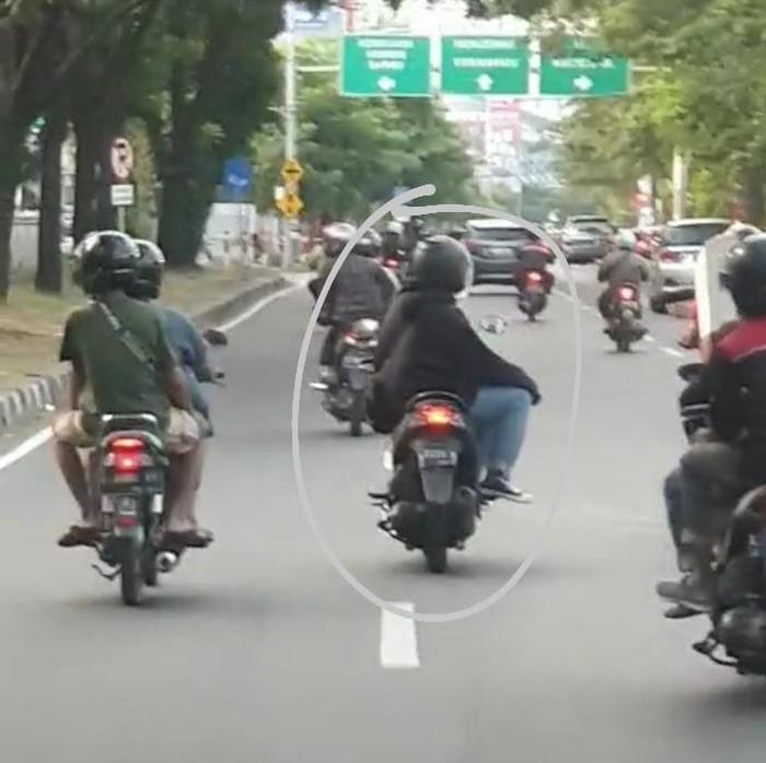 Seorang pengendara di Surabaya tengah diburu polisi. Sebab, ia terekam mengendarai motor dengan tidak wajar di jalan raya.