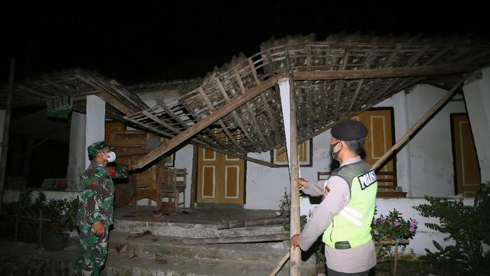 Personel kepolisian mengecek kondisi rumah warga yang rusak pascagempa di Desa Ploso Kecamatan Selopuro, Blitar, Jawa Timur, Jumat (21/5/2021). BPBD setempat masih mendata sejumlah kerusakan bangunan akibat gempa magnitudo 6,2SR yang terjadi sekitar pukul 19.09 WIB dan berpusat di lepas pantai selatan Blitar tersebut. ANTARA FOTO/Irfan Anshori/rwa.