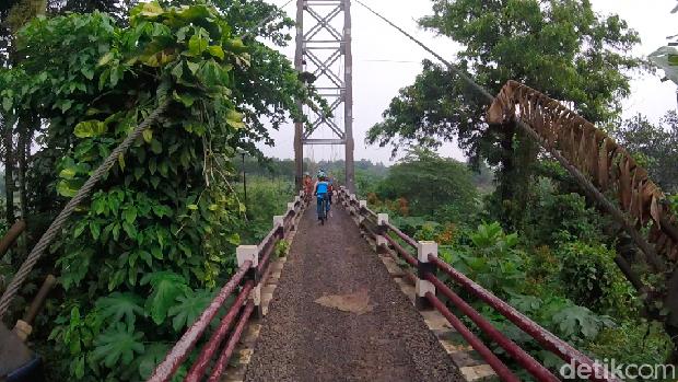 Pesepeda melewati jembatan gantung di Curug, Depok. Jembatan ini menghubungkan Depok dan Bogor