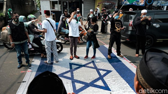 Sejumlah massa gelar aksi bela Palestina di Tangerang Selatan. Di tengah pelaksanaan aksi, massa tampak menginjak bendera Israel. Berikut penampakannya.