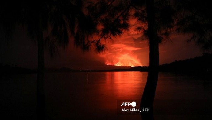 This general view taken on May 22, 2021 from Tchegera Island outsoide Goma on the lake Kivu in the East of the Democratic Republic of Congo shows flame spewing from the Nyiragongo volcano. - The famous Nyiragongo volcano, near the city of Goma, in the east of the Democratic Republic of the Congo (DRC), suddenly became active on Saturday evening, an AFP correspondent noted. Strong emanations of glowing light coming out of the crater were visible from Goma, while a smell of sulfur was perceptible in the city, located on the southern flank of the volcano, on the shores of Lake Kivu, he noted. (Photo by Alex Miles / AFP)