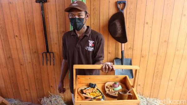 Setelah kita memesan makanan, pelayan di kafe ini membawa makanan yang kita pesan dengan menggunakan tray kayu, seperti sedang mengantar susu ke rumah pelanggan.
