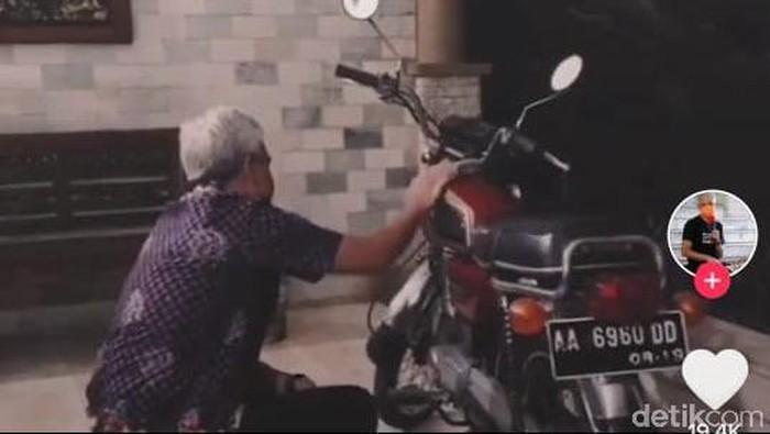 Ganjar Pranowo mengelap sepeda motor merahnya. (TikTok @ganjarpranowofc)