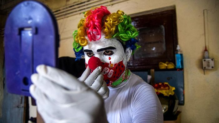 MUMBAI, INDIA - MAY 22: Ashok Jagannath Kurmi, a 36-year-old social worker, sprays disinfectant liquid while dressed in a clown costume at a slum on May 22, 2021 in Mumbai, India. Kurmi, 36, who works for a pharmaceutical company to earn money, says that he dresses in different costumes during his outreach to help spread official messages about the Covid-19 coronavirus to both children and adults. He says that dressing up in various ways, such as a clown, helps remind people to try and stay happy as well as healthy in the face of the unrelenting wave of infections that has swept India. Indias prolonged and devastating wave of Covid-19 infections has gripped cities and overwhelmed health resources. (Photo by Fariha Farooqui/Getty Images)