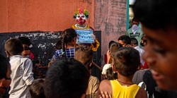 Seorang pekerja sosial berkeliling pemukiman kumuh dengan kostum badutnya. Aksinya ini untuk menyebarkan pesan bahaya Corona kepada anak-anak dan orang dewasa.