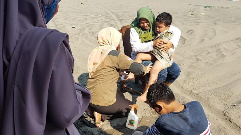 Wisatawan yang tersengar ubur-ubur di Pantai Parangtritis, Minggu (23/5).