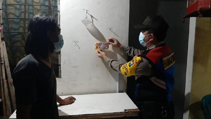Polisi Surabaya melakukan sosialisasi untuk mencegah penyebaran COVID-19. Polisi menempelkan stiker imbauan di rumah warga yang habis mudik, agar melakukan karantina dan tes swab.