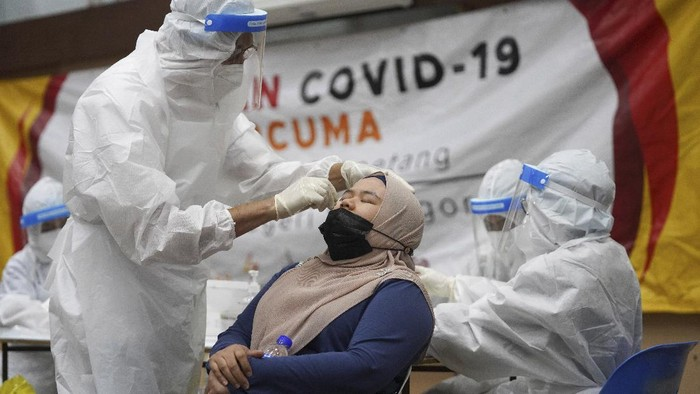 A medical worker collects a swab sample from a woman during coronavirus testing at a COVID-19 testing center in Ulu Klang, on the outskirts of Kuala Lumpur, Malaysia, Tuesday, May 18, 2021. (AP Photo/Vincent Thian)