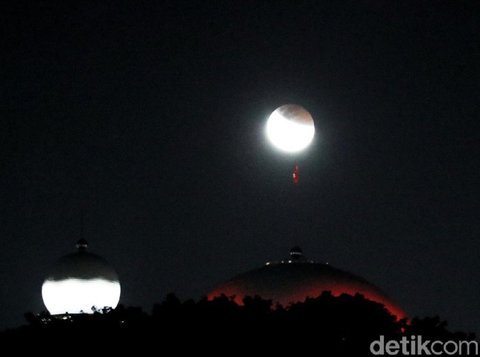 Fenomena langka gerhana bulan yang terjadi langsung diabadikan. Fotografer detikcom Pradita Utama memadukan potret gerhana dengan simbol ikonik di Jakarta.