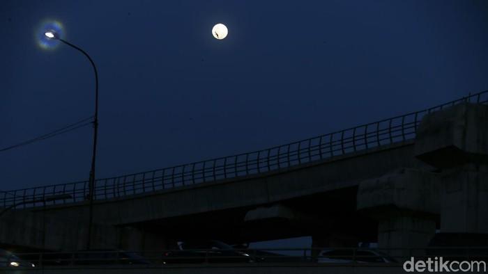 Warga saat melintas di jembatan penyeberangan orang (JPO), di kawasan Cawang, Jakarta Timur, dengan latar belakang panorama bulan.