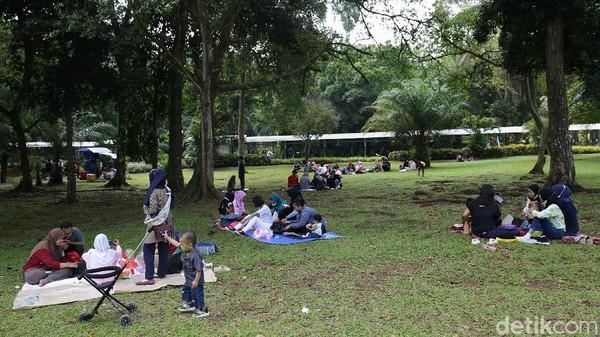 Sebagian warga beristirahat dengan menggelar tikar di taman yang rindang usai berkeliling melihat aneka satwa.