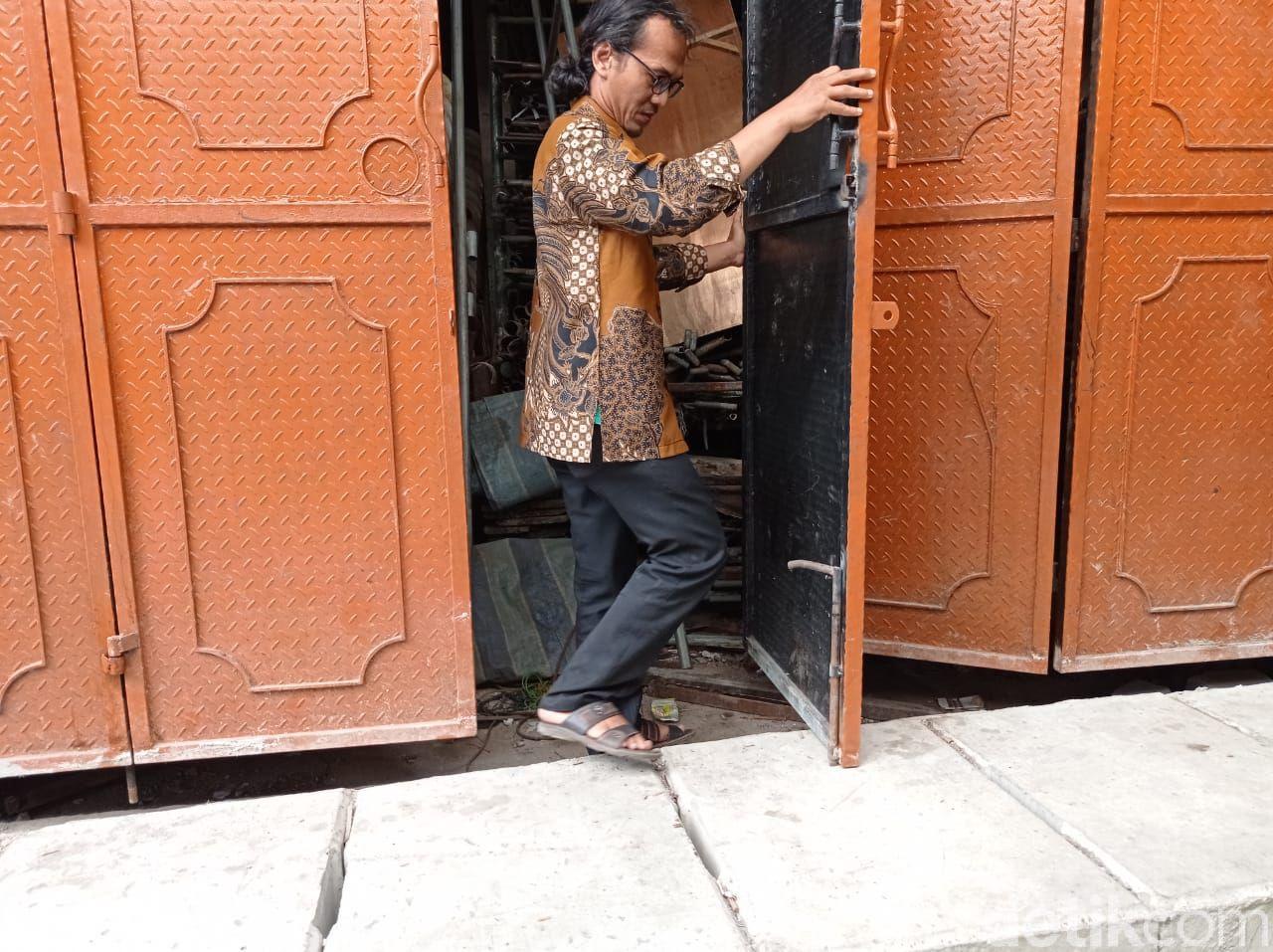 Agung Rahadian menunjukkan daun pintunya yang masih mentok dengan penutup got. 27 Mei 2021. (Sachril Agustin Berutu/detikcom)