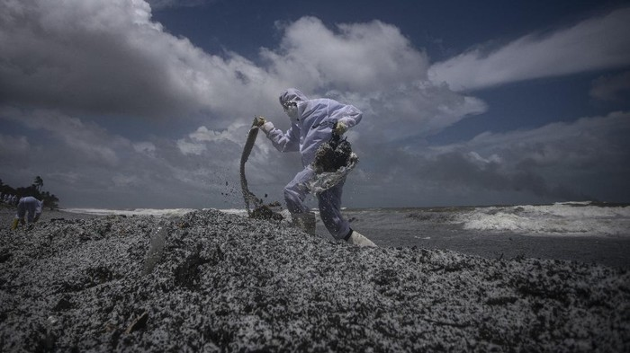 A Sri Lankan navy soldier clad in a protective suit walks on the mounds of debris that washed ashore from the burning Singaporean ship MV X-Press Pearl which is anchored off Colombo port at Kapungoda, out skirts of Colombo, Sri Lanka, Thursday, May 27, 2021. (AP Photo/Eranga Jayawardena)
