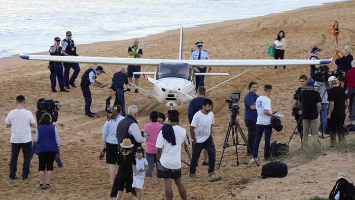 Spectators stand near a light plane that made an emergency landing on a beach in Sydney Wednesday, May 26, 2021. The recreational plane landed safely on a Sydney beach with three people aboard including a baby on Wednesday after its single engine failed, officials said. (AP Photo/Mark Baker)