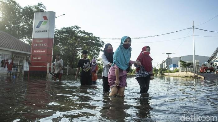 Seorang anak bermain di kawasan Muara Baru, Jakarta Utara, Kamis (17/5/2021). BMKG mengingatkan fenomena gerhana bulan total atau Super Blood Moon berpengaruh terhadap kondisi pasang air laut maksimum.
