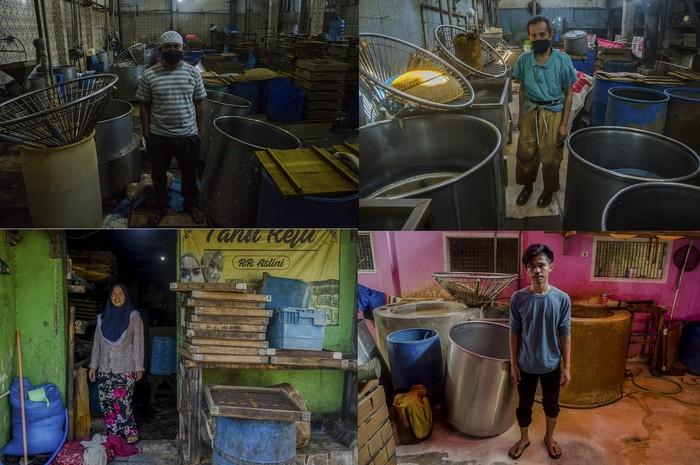 Pekerja merapikan alat produksi saat aksi mogok pabrik pembuatan tahu di Sentra Industri Perajin Tahu Cibuntu, Bandung, Jawa Barat, Jumat (28/5/2021). Seluruh Industri Perajin Tahu di kawasan tersebut melakukan aksi mogok produksi mulai dari 28 mei hingga 30 mei akibat tingginya harga bahan baku kedelai yang mencapai Rp11 ribu sehingga mengganggu biaya produksi dan harga penjualan tahu ke masyarakat. ANTARA FOTO/Novrian Arbi