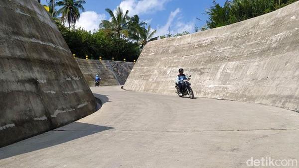 Pengendara sepeda motor melintas di jalan berkelok yang menuju sabo dam.