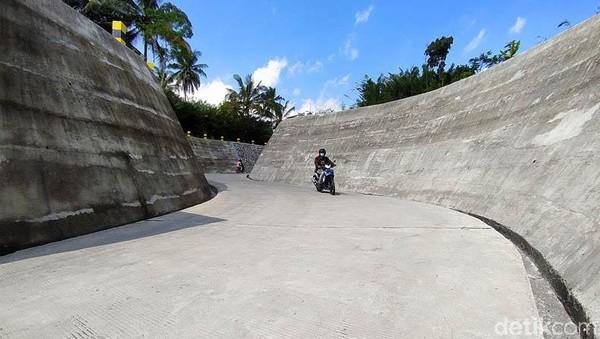 Kemudian, di sisi kanan dan kiri jalan yang berkelok itu terdatap dinding atau tembok penahannya.