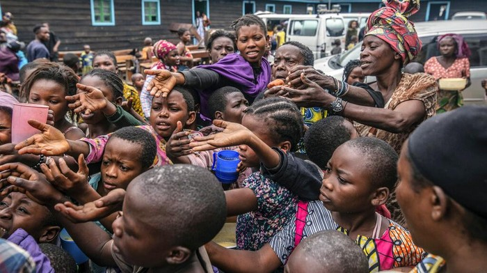 People who fled Goma, Congo, gather at a food distribution point Friday, May 28, 2021 in Sake, some 25 kms (16 miles) west of Goma where they found shelter following an official evacuation order five days after Mount Nyiragongo erupted. (AP Photo/Moses Sawasawa)