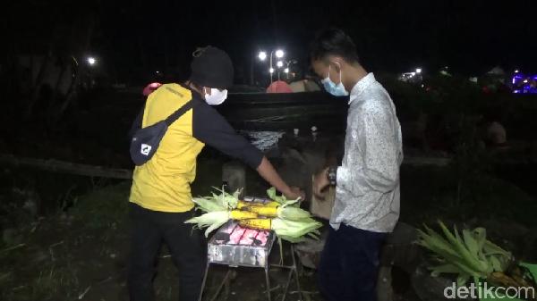 Selain bermalam di tenda di samping kolam renang, suasana malam sambil membakar jagung dan menikmati bersama keluarga di kaki Gunung Semeru sangat menyenangkan dan wajib traveler coba. (Nur Hadi Wicaksono/detikTravel)