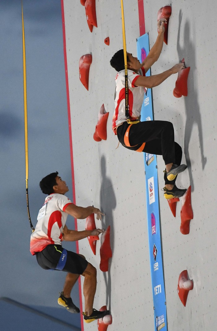 First-place finisher Veddriq Leonard, center, of Indonesia, stands with second-place Kiromal Katiban, left, of Indonesia, and third-place Marcin Dzienski, of Poland after the men's speed climbing finals at the climbing World Cup on Friday, May 28, 2021, in Salt Lake City. (AP Photo/Alex Goodlett)