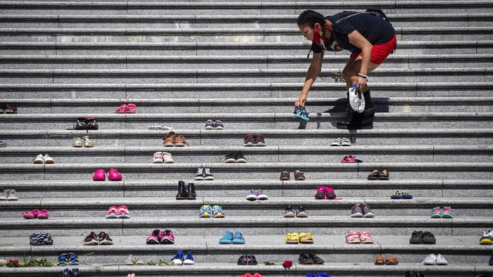 Lorelei Williams places one of 215 pairs of childrens shoes on the steps of the Vancouver Art Gallery as a memorial to the 215 children whose remains have been found buried at the site of a former residential school in Kamloops,  in Vancouver, British Columbia, Canada on Friday, May 28, 2021. Chief Rosanne Casimir of the Tkemlups te Secwépemc First Nation said in a news release Thursday that the remains were confirmed last weekend with the help of a ground-penetrating radar specialist.  (Darryl Dyck/The Canadian Press via AP)