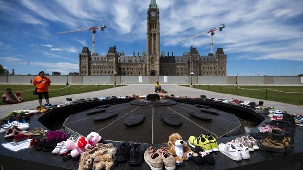 Shoes line the edge of the Centennial Flame on Parliament Hill in memory of the 215 children whose remains were found at the grounds of the former Kamloops Indian Residential School at Tk'emlups te Secwépemc First Nation in Kamloops, British Columbia, on Sunday, May 30, 2021, (Justin Tang/The Canadian Press via AP)